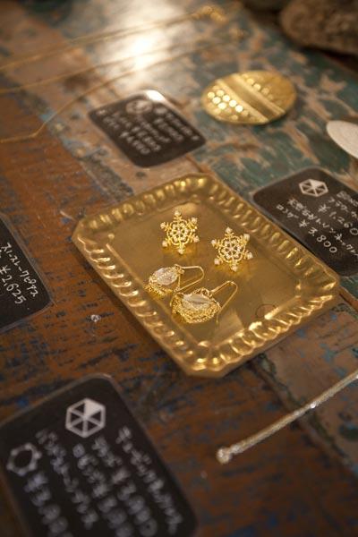 さりげなく邪魔にならないゴールドカラーのアクセサリー。スノーフレークピアス¥2,625、クリスタルピアス¥4,500